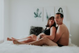 couple assis sur le lit dans la chambre, avec femme enceinte grossesse a montpellier