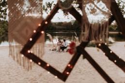 couple de mariée à leur table de mariage sur le sable. mariage en octobre. décotain de mariage avec cadre photo et macramé. Herbe de pampa, mariage bohème, vintage, champêtre et sauvage. Plus belle photo de mariage du monde