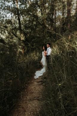couple de mariés dans la forêt, robe de mariage en soie et longue traine