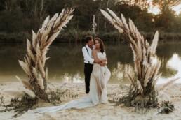 couple de mariés sous une arche de cérémonie en pampa. mariage en automne. robe de mariage bustier et traine. mariage au bord de l'eau