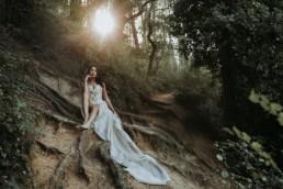 mariée assise par terre dans la forêt, robe de mariage en soie légère plaqué sur les racines des arbres. robe de mariée à bustier
