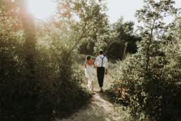 mariés dans une prairie pour un mariage en automne. Robe bustier avec traine en mousseline