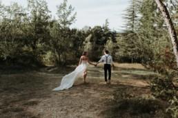 mariés qui marche dans une prairie en provence. plus belle photo de mariage