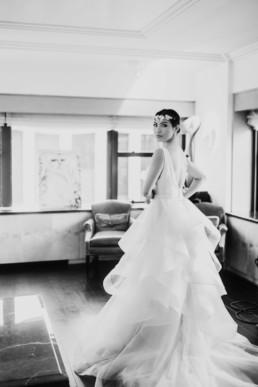 femme avec robe de mariée de créateur a volant et couronne de fleur pendant les préparatifs du mariage