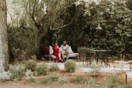 photographe de mariage aux baux de provence, invités d'honneurs afro américain qui discute sur un banc en fer forgé