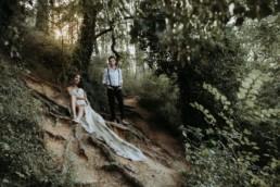 couple de mariés dans la foret assise par terre. robe bustier, homme chemise et bretelle