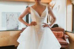 photo mariée main sur la taille.détail de la robe en soie et décolleté. Boucle oreille pendant en diamant