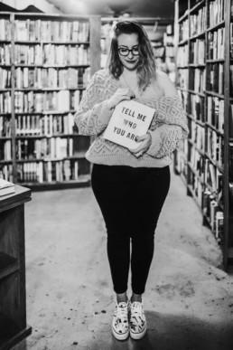 portrait en noir et blanc d'une femme a lunette, chaussures vans, à la bibliothèque the last bookstore de los angeles
