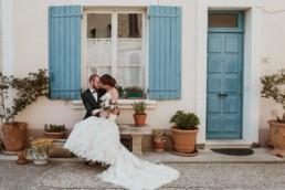 des mariés assis sur un banc en provence, devant une maison de village aux volets bleus charrettes