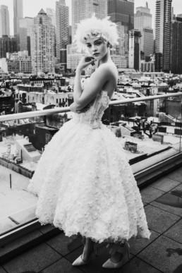 une jeune mariée sur un rooftop de new york. Robe de mariée style marilyne monroe, couronne de plume dans les cheveux