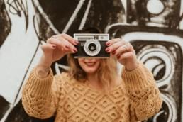 femme qui tiens un appareil photo vintage derrière un mur de tags à montpellier