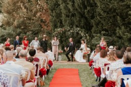 allée d'une cérémonie laïque de mariage en plein air, à Arles. Tapis rouge, arche de cérémonie en lierre et épi de blé