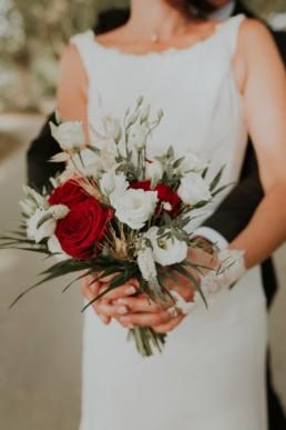 le bouquet de la mariée dans ses mains devant sa robe de mariage. Bouquet rouge et blanc à Béziers