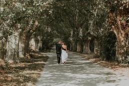 couple de mariés qui marchent sous les platanes à Gordes, apres la cérémonie laïque en plein air