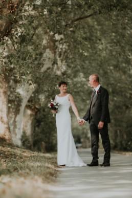 les mariés qui se tiennent la main au grau du roi. Costume de mariage noir, robe de mariée sirène