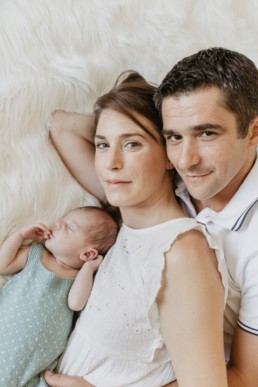 photo parents et bébé allongés sur le lit au grau du roi