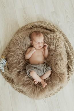 un bébé qui dort dans son couffin en peau de lapin et un bloomer vert, à la maison au Grau-du-Roi en Lagueddoc-Roussillon