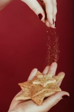 saupoudrer des paillettes sur des petits sablés de noel en forme d'étoile. Pâtisserie à Lattes, près de Montpellier