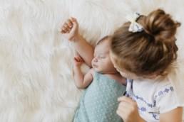 nouveau-né qui dort dans les bras de sa grande soeur à Castelnau-le-Lez