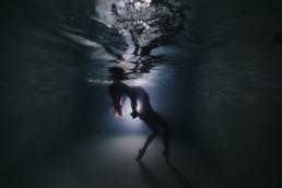 Femme qui remonte à la surface de l'eau les bras en arrière pour des portraits aquatiques à Montpellier
