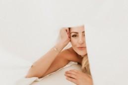 jeune femme blonde sexy et toute nue sous les draps dans un lit à bézier