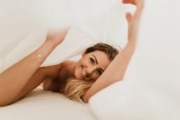 portrait de femme blonde sous les draps qui joue et sourie, à la grande motte
