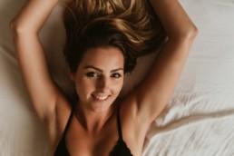femme blonde en lingerie noire allongé sur le lit. Les bras en arrière, vue de dessus, dans son appartement à montpellier