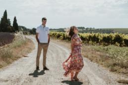 couple qui pose pour des photos de faire-part a cote des lavandes et des vignes dans le Vaucluse. Femme robe longue à fleur