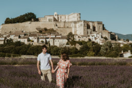couple devant le chateau de grignan, dans le champ de lavande avant le mariage. Robe longue à fleur