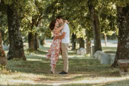 couple qui s'embrassent sous une allée de platane à Montpellier. Femme sur la pointe des pieds