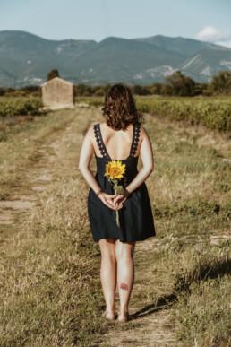 femme au pied du luberon dans un champ de vigne avec un tournesol. tatouage coquelicot sur le mollet droit