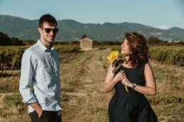couple dans un vignoble avec un tournesol, lunette de soleil, luberon en arrière plan
