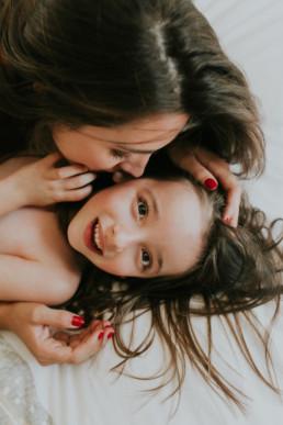 photo d'une maman qui fait un bisous sur la joue a sa fille dans la chambre à Eyguieres