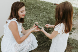 scene de vie dans un potager a montpellier ou une fillette ramasse des légumes avec sa maman