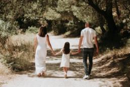maman papa et fillette sur un cehmeni de campagne qui promènent mais dans la main le jour de la fête des mères
