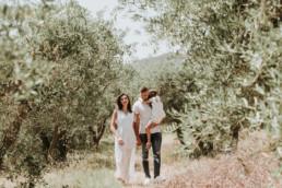 une photo d'une famille qui marche dans la nature entourée de champ d'olivier