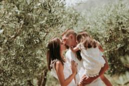 baiser d'une couple de jeune mariée avec leur petite fille dan les bras lors d'une promenade en Provence