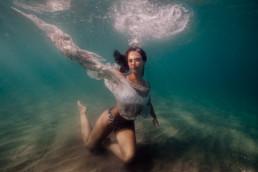 photo femme sous l'eau dans la mer avec drapeau blanc