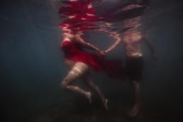 couple femme enceinte dans l'eau en robe rouge, à montpellier frontignan plage
