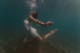 photo de femme dans la mer à Carnon 34 en robe blanche. Shooting photo subaquatique dans la mer avec le reflet et les rayons du soleil qui traverse l'eau. femme qui danse dans l'eau