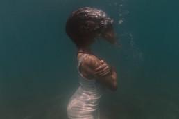photo poétique d'une femme sous l'eau dans la mer à Sérignane dans l'Hérault. Cheveux de femme qui bougent dans l'eau et bulles qui remontent à la surface. Femme dans l'eau en robe blanche
