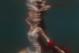shooting photo, une femme dans l'eau, avec le visage qui remonte a la surface. reflet d'un portrait à la surface de l'eau, voile rouge, robe blanche,