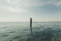 photo femme dans la mer jusqu'aux genoux. Plage du 34 montpellier, jeune femme sportive, maillot de bain, shooting photo le matin en juillet