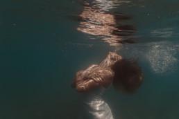 photo subaquatique portrait femme sous l'eau à la plage de aigues-mortes. Cheveux mouvement dan l'eau, bulles qui remontent à la surface, reflet portrait à la surface de l'eau