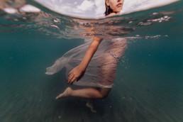 photo d'une femme qui marche dans la mer, le visage à l'extérieur, avec un voile blanc sur le corps à frontignan