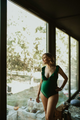 femme blonde enceinte en maillot de bain vert contre une baie vitrée à Montpellier odysseum pour une reportage photo grossesse et famille pour l'arrivée du deuxième enfant.