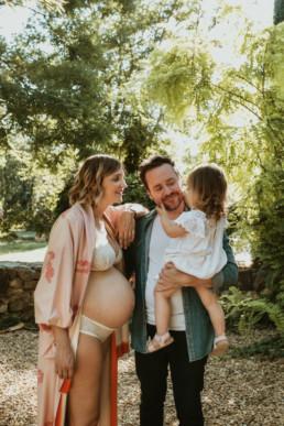 photo de famille avec la maman enceinte , et le papa qui tiens sa fille dans les bras, pour un reportage photo grossesse à montpellier quater odysseum