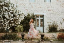 femme enceinte en robe longue a fleur, qui danse dans son jardin à Montpellier Odysseum, avec un chapeau de paille sur la tête. Meilleure photographe de Montpellier, Juvignac, Mauguio, Saint-Aunes et vendargues
