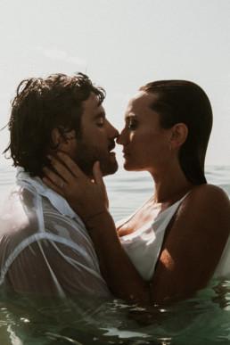 une femme et un homme, un couple qui s'embrasse a montpellier dans la mer à la plage