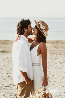 couple de marié sur la plage a montpellier pour un day after sur le sable et dans l'eau. mariée avec un chapeau et bouquet bohème